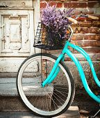 stock photo of wooden basket  - Vintage bycycle with basket with lavender flowers near the old wooden door - JPG