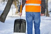 stock photo of snow shovel  - Man with a snow shovel on the sidewalk in winter - JPG