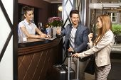 stock photo of mood  - Young couple upon arrival at hotel reception - JPG