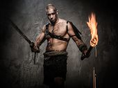 picture of legion  - Wounded gladiator holding torch and sword covered in blood  - JPG
