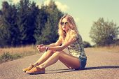stock photo of independent woman  - Trendy Hipster Girl Sitting on the Road - JPG