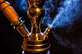 foto of tobacco-pipe  - Water pipe or hookah with blue smoke