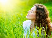 stock photo of lie  - Beautiful Spring Young Woman Outdoors Enjoying Nature - JPG