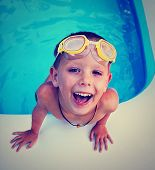 picture of rubber mask  - a young boy swimming in a small pool done with a vintage retro instagram filter - JPG