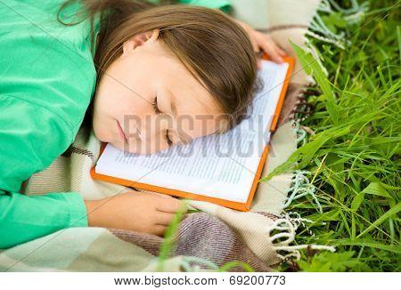 Little girl is sleeping on her book outdoors