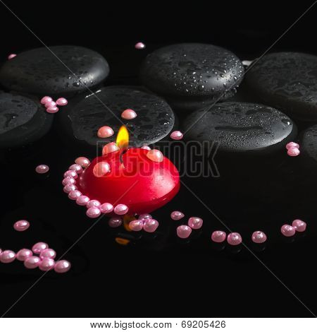 Spa Setting Of Orchid Cambria Flower On Zen Stones With Drops, Pearl Beads And Red Candles In Reflec