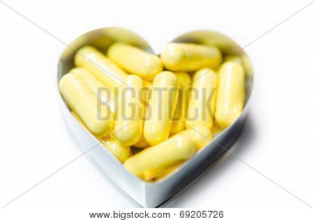 Yellow Food Supplemnet Coq10 (co-enzyme Q10) Capsules In Heart Shape Box Closeup On White Background