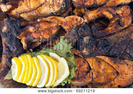 Fried fish on fire with lemon wedges and green
