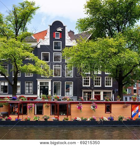 Amsterdam canal with houseboat and historic architecture