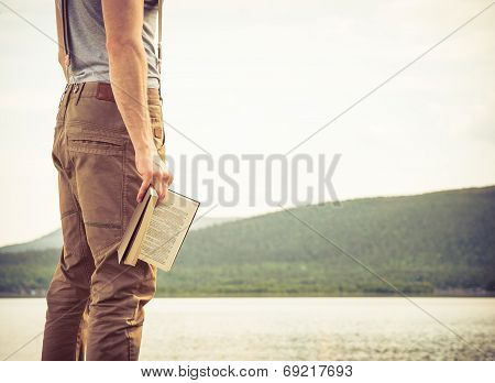 Young Man With Book Outdoor Lake On Background Summer Vacations And Lifestyle Concept