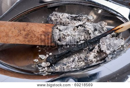Burned Match And Ashes In A Metal Ashtray