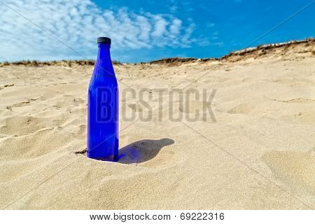 Blue water bottle standing in dry sand