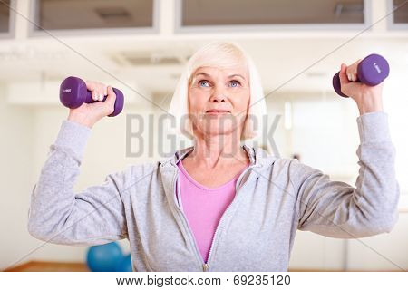 Portrait of aged woman doing exercise with barbells