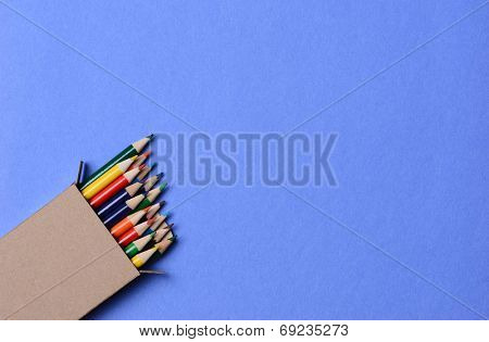 High angle shot of a box of multi-colored pencils on a blue background. The pencils are part way out of the box which is at an angle in the lower left corner leaving copy space.