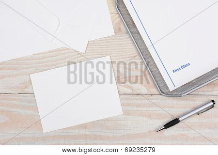 Envelopes and paper for writing letters via snail mail. High angle shot with in-box and pen on a whitewashed desk.