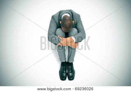 a businessman curled up in the floor with his head between his knees