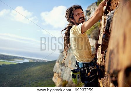A rock climbing man with dreadlocks smiling at the camera while climbing up a steep mountain with a harness
