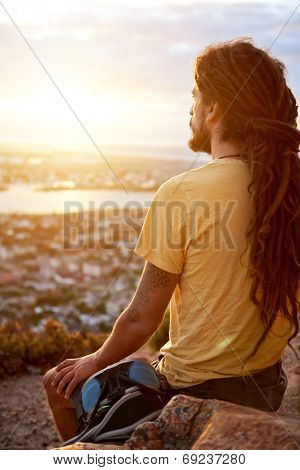 A man in dreadlocks on a mountain looking at the view