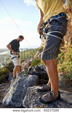 Men applying their harness and climbing equipment in preparation to go rock climbing
