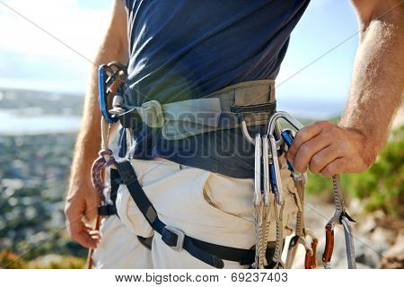 Close up of a man in his harness and rock climbing equipment