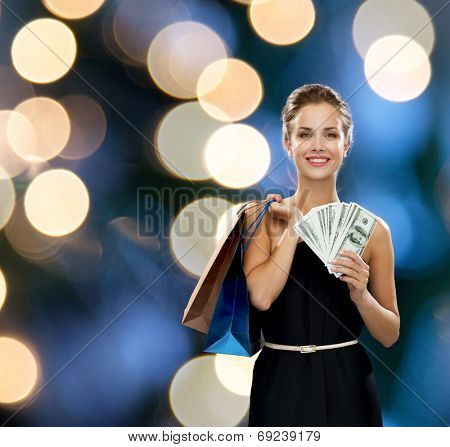 shopping, sale, gifts, money and holidays concept - smiling woman in dress with shopping bags and money over black background