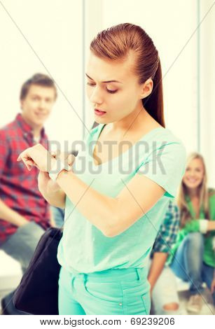 education and time management concept - student girl looking at wristwatch