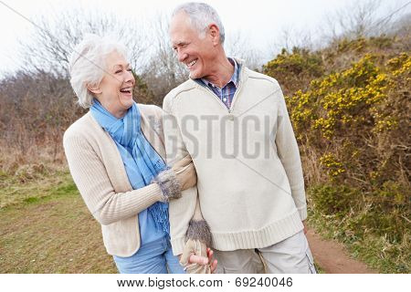 Senior Couple Walking Through Winter Countryside