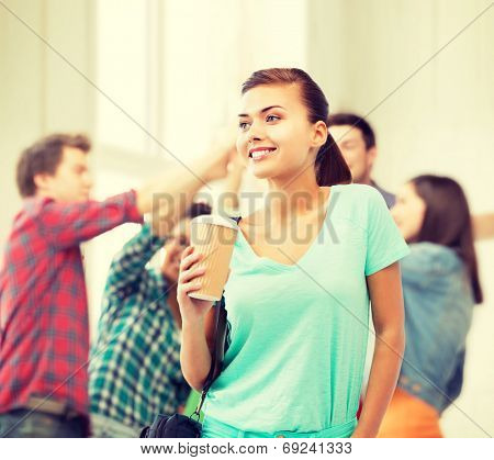 education concept - student holding take away coffee cup in college
