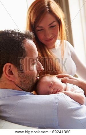 Parents At Home With Sleeping Newborn Baby Daughter
