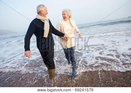 Senior Couple Walking Along Winter Beach