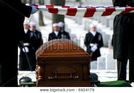Honor Guard holding flag over casket