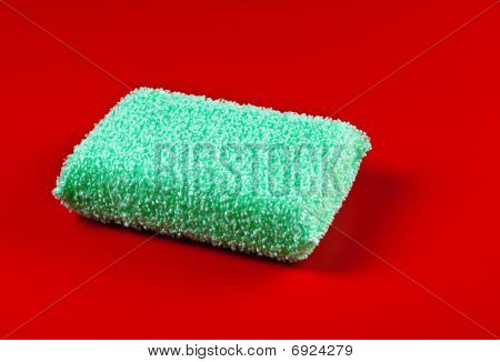 Green Sponge On Red Background