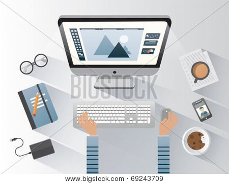 Designer working on computer at desk on grey background