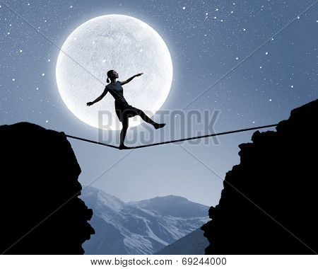 Silhouette of woman balancing on rope above gap