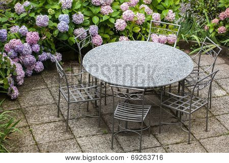 table and chairs in garden with color hydrangea flowers