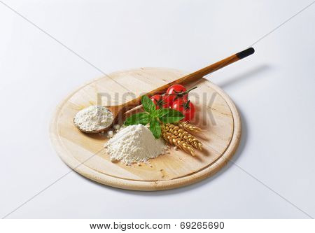 cutting board with soft wheat flour, wooden spoon, wheat ear and fresh tomatoes