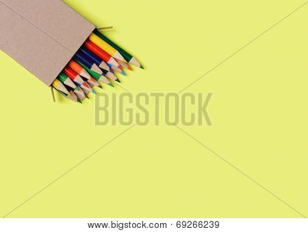 High angle shot of a box of multi-colored pencils on a yellow background. The pencils are part way out of the box which is at an angle in the lower left corner leaving copy space.