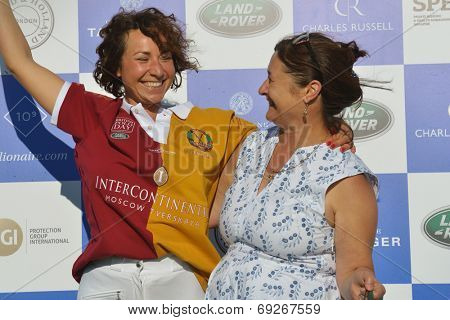 TSELEEVO, MOSCOW REGION, RUSSIA - JULY 26, 2014: Inna Rodzianko give the gift to Maria Agranovska of Tseleevo Polo Club during the British Polo Day. Tseleevo Polo Club hosts the event for the 2nd time