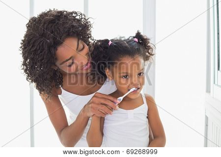 Pretty mother helping her daughter brush her teeth at home in the bathroom
