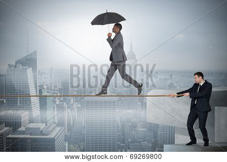 Young business man pulling a tightrope for businessman against misty cityscape