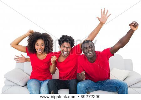 Football fans in red cheering on the sofa on white background