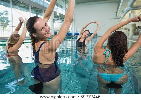 Female fitness class doing aqua aerobics on exercise bikes in swimming pool at the leisure centre