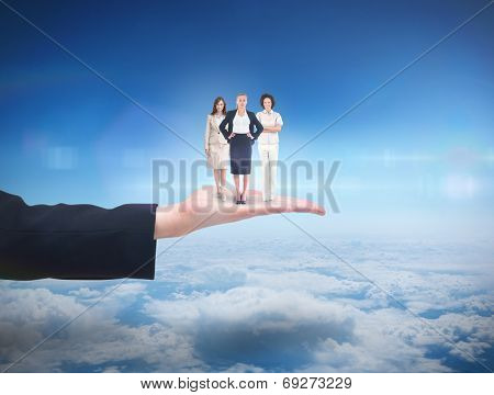 Team of businesswomen looking at camera against blue sky over clouds at high altitude