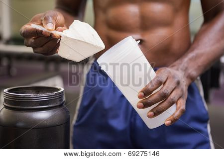 Mid section of a body builder holding a scoop of protein mix in gym