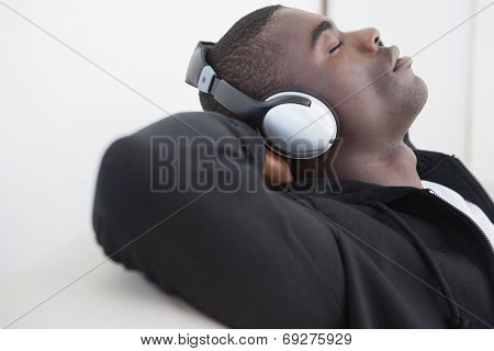 Casual man sitting on sofa enjoying music with eyes closed at home in the living room