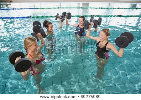 Smiling female fitness class doing aqua aerobics with foam dumbbells in swimming pool at the leisure centre