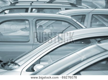 Telephoto image of cars parked in car park (blue toned)