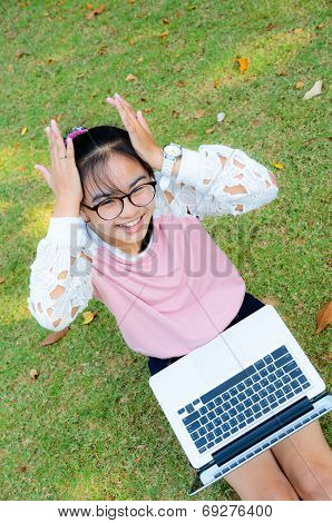 Cute Girl Is Happy With Notebook On Grass