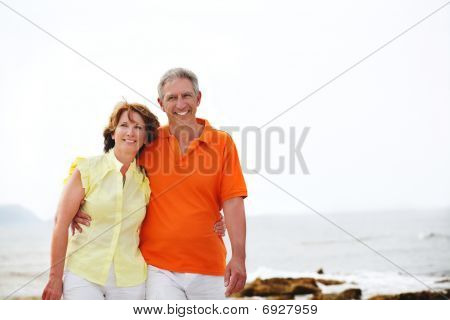 Mature couple walking along the beach.