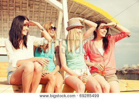summer holidays and vacation concept - smiling girls with drinks on the beach searching for someone or something
